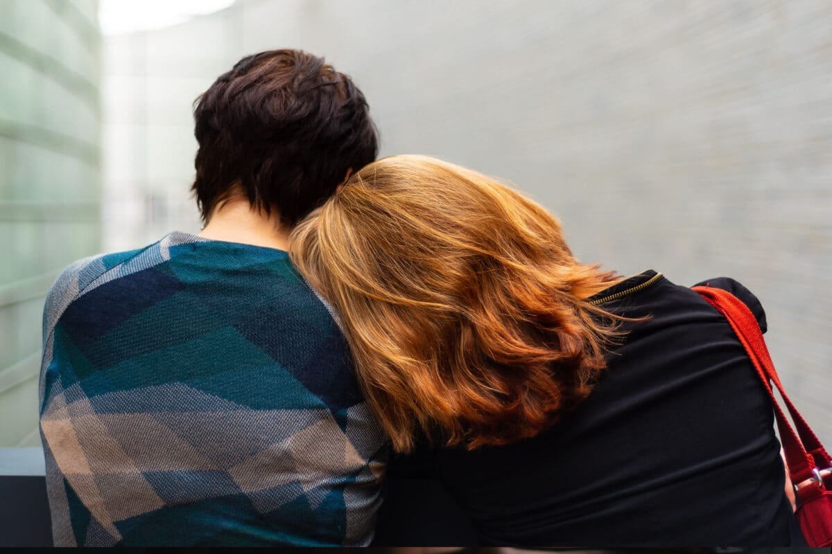 man and woman sitting with back
