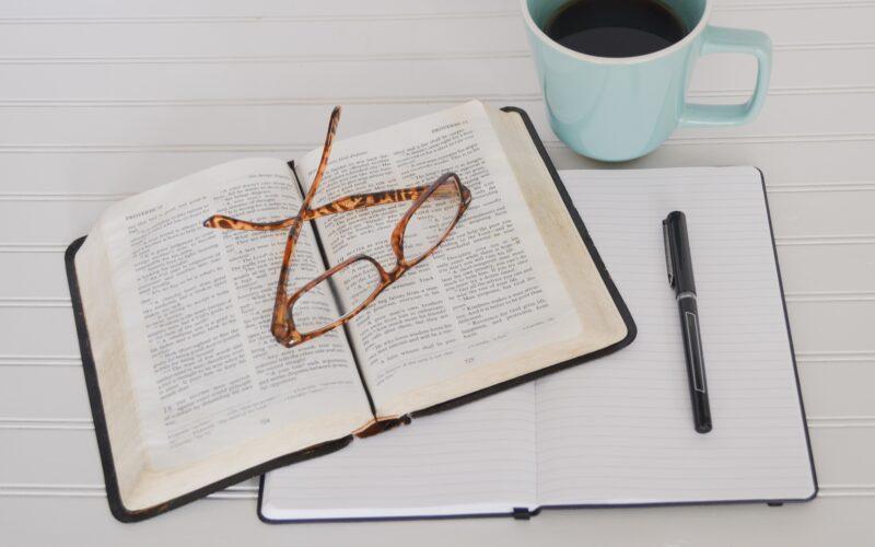 Bible and journal on table with mug of black coffee