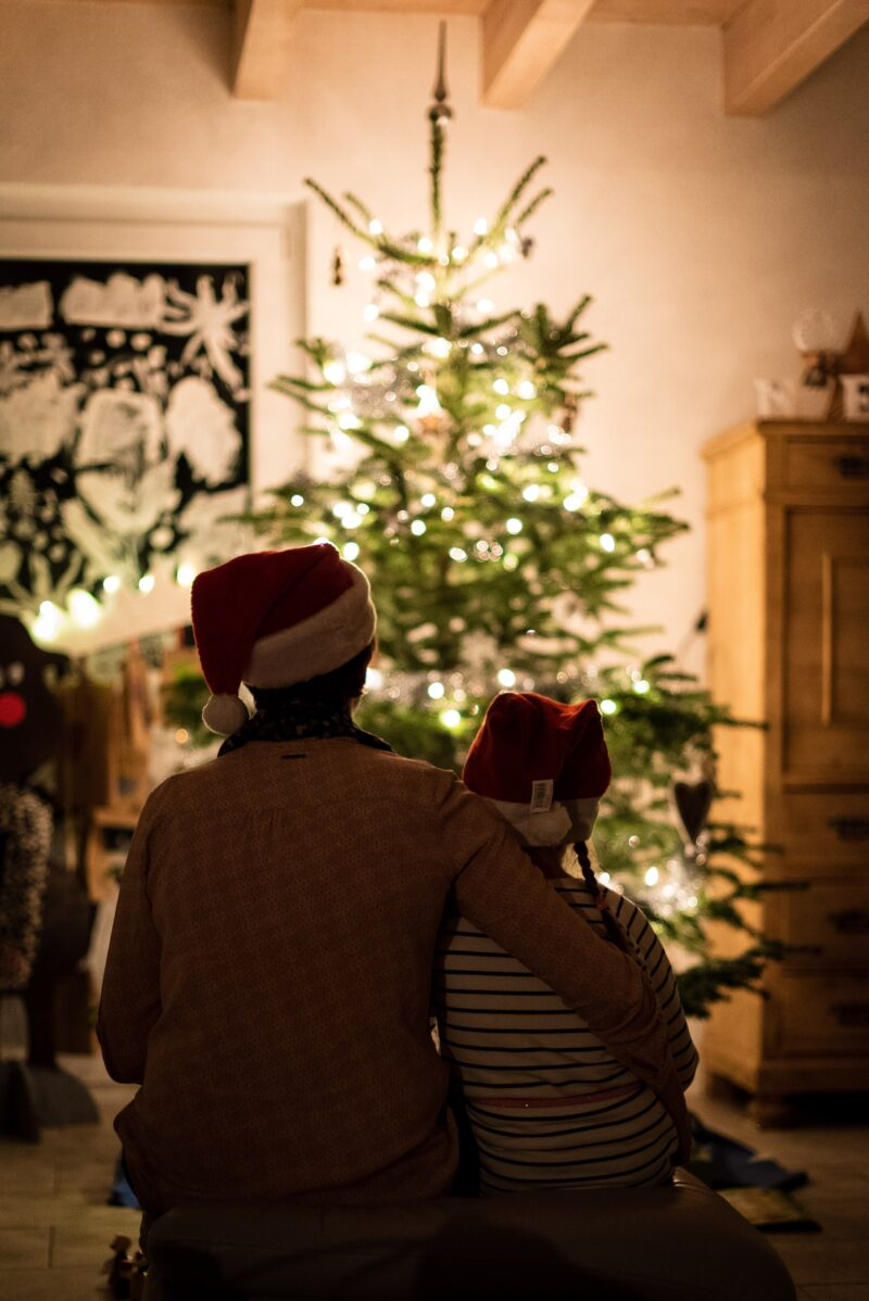 Father and child sitting in front of Christmas tree