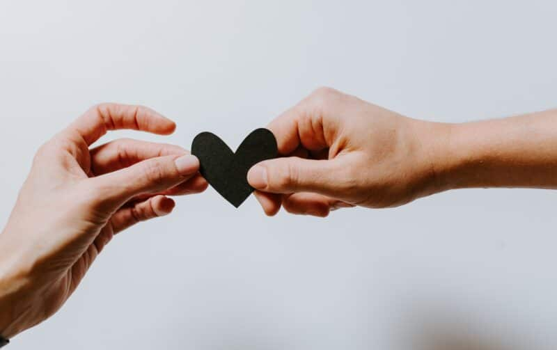 Two hand holding black paper heart